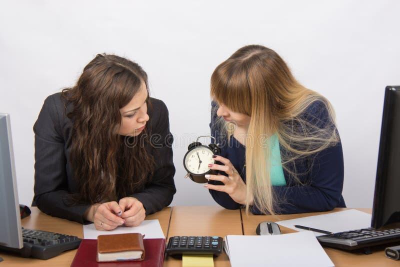 Due ragazze nell'ufficio che attendono la conclusione del giorno e dello sguardo all'orologio fotografia stock libera da diritti