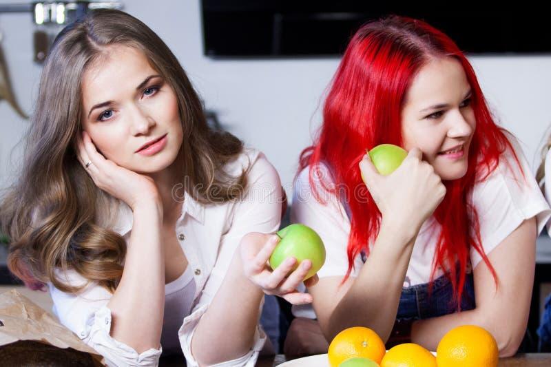 Due ragazze nella cucina che parlano e che mangiano immagine stock libera da diritti