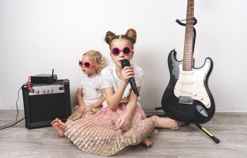 Due ragazze in occhiali da sole rosa e magliette identiche cantano con un microfono e giocano la chitarra elettrica fotografia stock libera da diritti