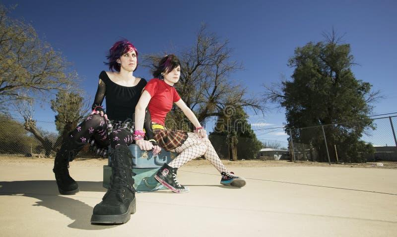 Due ragazze punk che si siedono sulle valigie fotografia stock