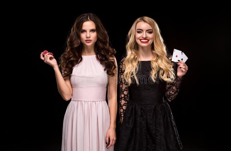 Due ragazze sexy castane e bionda, posante con i chip in sue mani, fondo del nero di concetto della mazza immagini stock