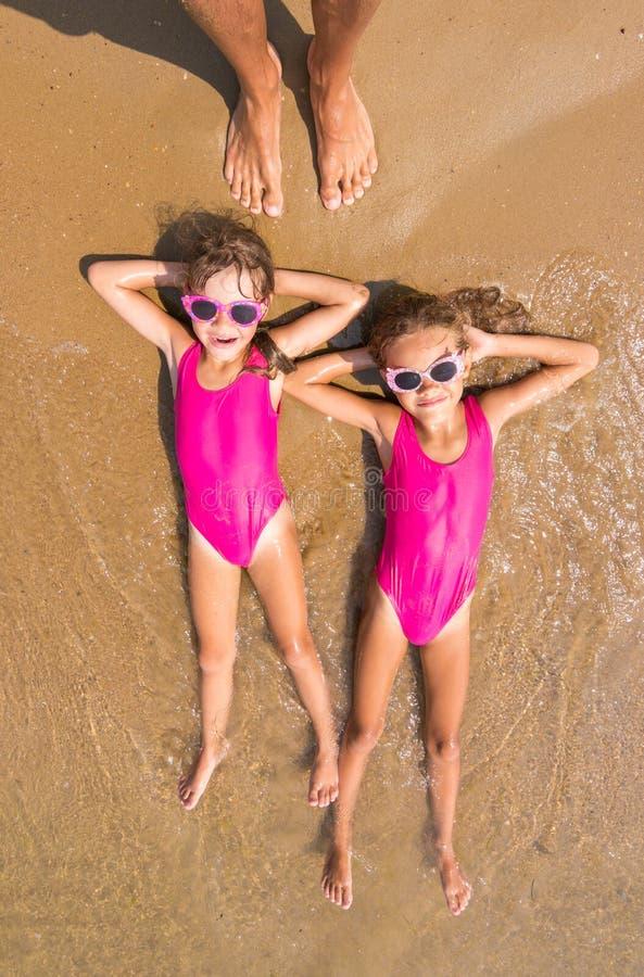 Due ragazze si trovano sulla sua parte posteriore su spuma della spiaggia sabbiosa del mare, là sono una serie di piede umano adu immagine stock libera da diritti