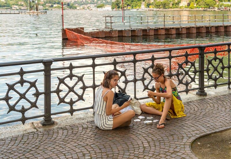 Due ragazze sono carte da gioco sulla passeggiata del lago Como in un giorno di estate caldo nel centro di Como, Italia immagine stock