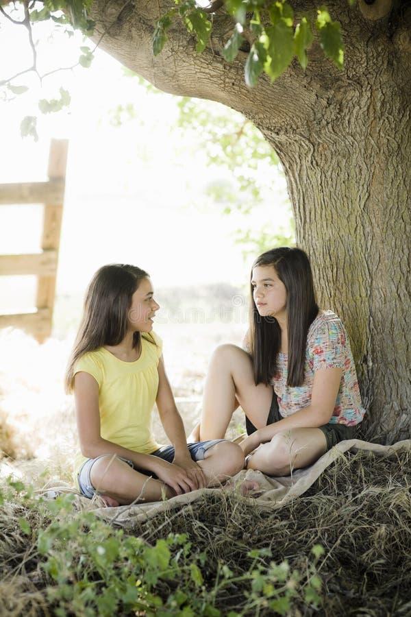 Due ragazze sotto un albero fotografia stock libera da diritti