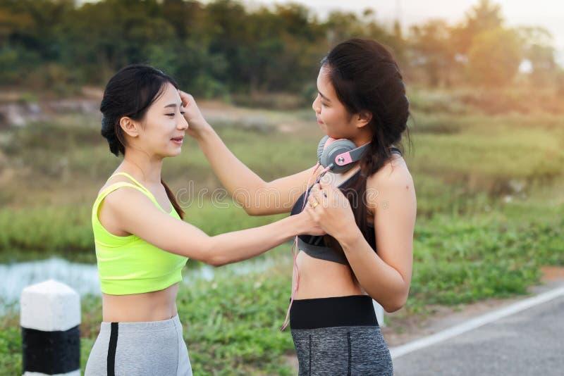 Due ragazze sportive che parlano divertimento e che toccano capelli per rilassarsi insieme in parco immagini stock