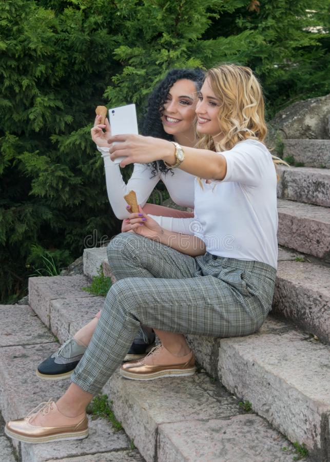 Due ragazze stanno prendendo i selfies e stanno mangiando il gelato immagine stock
