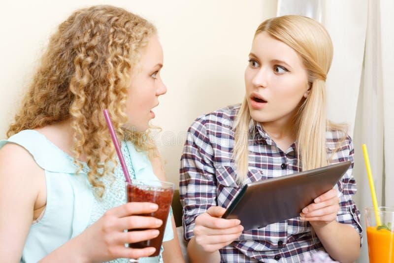 Due ragazze stupite con la compressa in caffè immagine stock libera da diritti