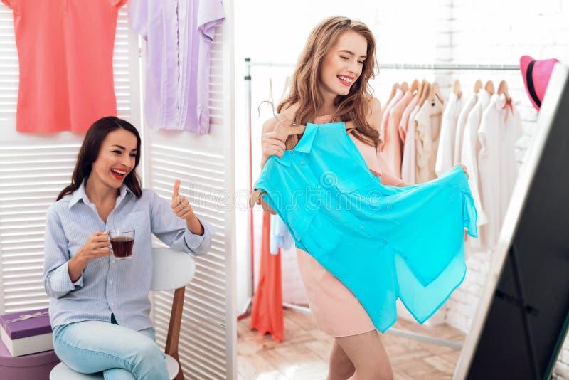 Due ragazze su acquisto Le ragazze scelgono i vestiti nel deposito Ragazze nella sala d'esposizione fotografie stock