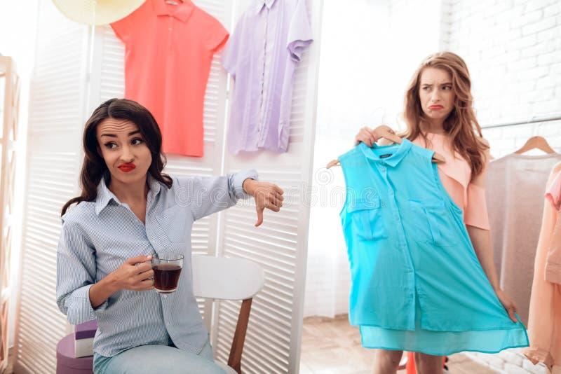 Due ragazze su acquisto Le ragazze scelgono i vestiti nel deposito Ragazze nella sala d'esposizione fotografie stock libere da diritti