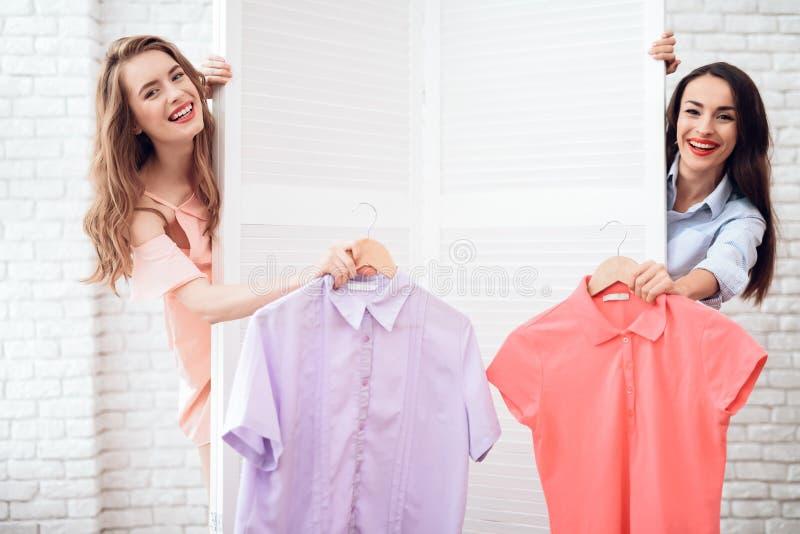 Due ragazze su acquisto Le ragazze scelgono i vestiti nel deposito Ragazze nella sala d'esposizione fotografia stock libera da diritti