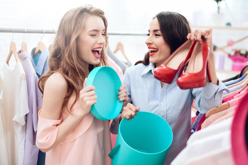Due ragazze su acquisto Le ragazze scelgono i vestiti nel deposito Ragazze nella sala d'esposizione immagine stock