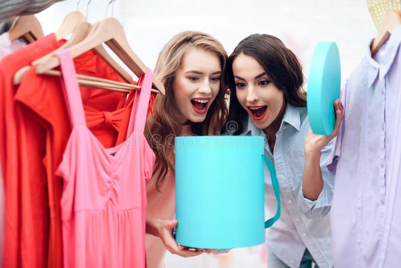 Due ragazze su acquisto Le ragazze scelgono i vestiti nel deposito Ragazze nella sala d'esposizione immagini stock libere da diritti