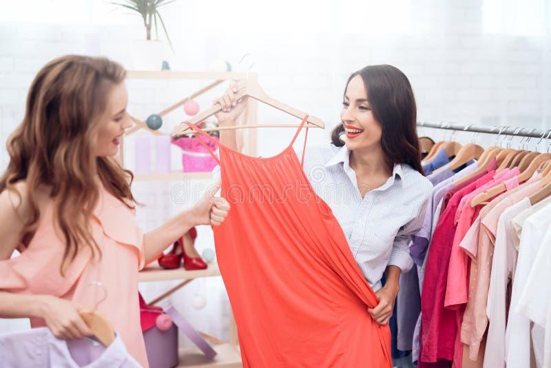Due ragazze su acquisto Le ragazze scelgono i vestiti nel deposito Ragazze nella sala d'esposizione immagine stock libera da diritti