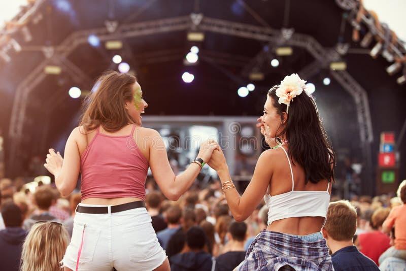 Due ragazze sulle spalle nella folla ad un festival di musica fotografia stock
