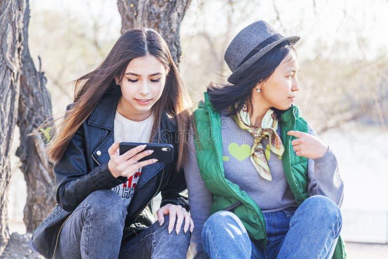 Due ragazze teenager delle amiche asiatiche sedersi nel parco e guardare il telefono, la generazione di digitale fotografia stock
