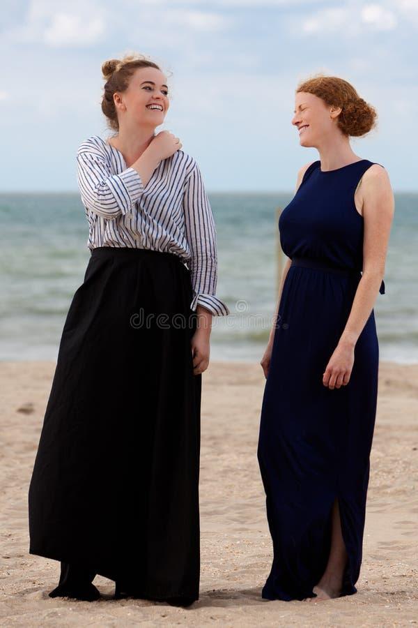 Due ragazze tirano il mare in secco della sabbia che ridono, De Panne, Belgio fotografie stock libere da diritti