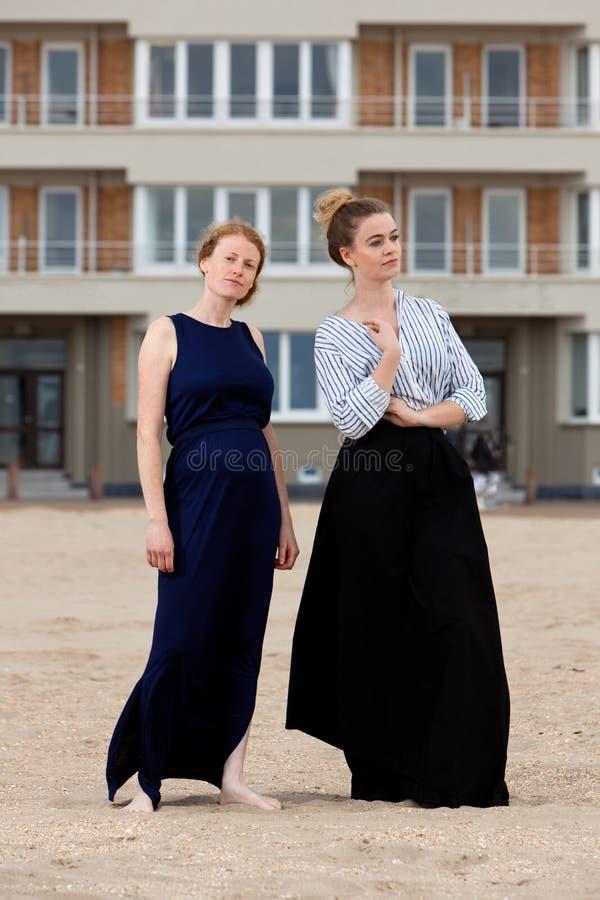 Due ragazze tirano la costruzione in secco di appartamento della sabbia, De Panne, Belgio immagini stock libere da diritti