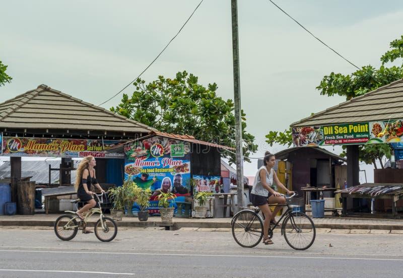 Due ragazze turistiche che guidano le biciclette sulla via fotografia stock libera da diritti