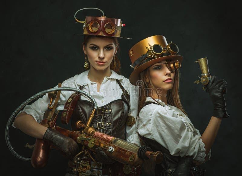 Due ragazze vestite nello stile di steampunk con le armi immagine stock libera da diritti