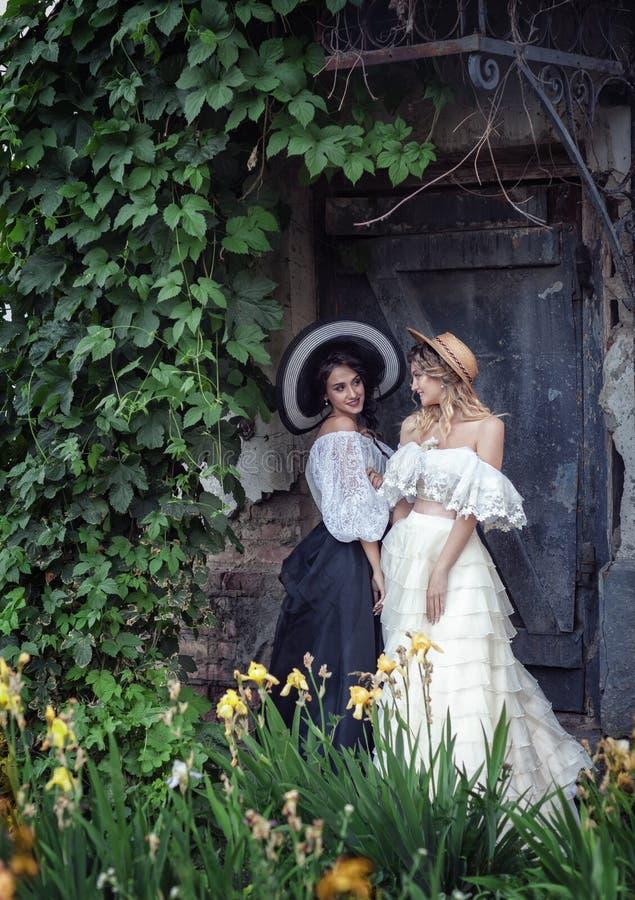 Due ragazze in vestiti d'annata e cappelli fotografie stock libere da diritti