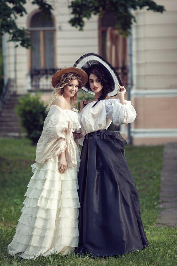 Due ragazze in vestiti d'annata e cappelli immagini stock