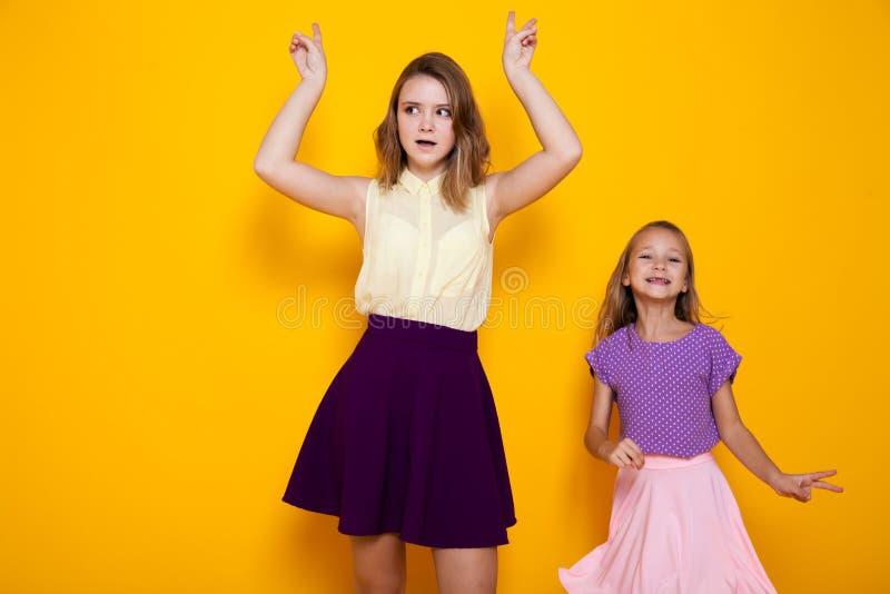 Due ragazze in vestiti variopinti stanno ridendo su un fondo giallo immagine stock libera da diritti