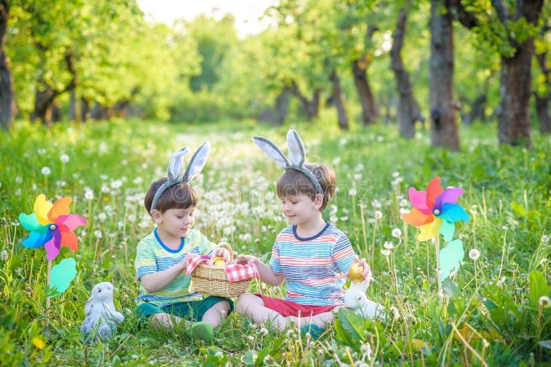 due ragazzi allegri si siedono sul prato inglese dopo le uova di Pasqua cercano fotografia stock
