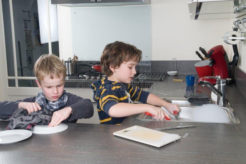 Due ragazzi che fanno i piatti immagine stock