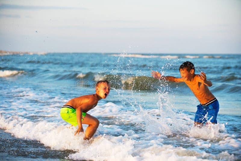 Due ragazzi che giocano alla spiaggia con acqua fotografia stock libera da diritti