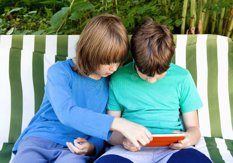 Due ragazzi che giocano con la compressa immagini stock