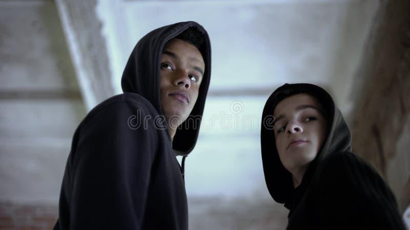 Due ragazzi che guardano indietro, impaurito essere preso per il crimine commettente, circospetto fotografia stock