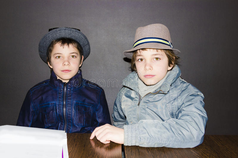 Due ragazzi che portano i cappelli ad una tavola in un caffè immagine stock libera da diritti