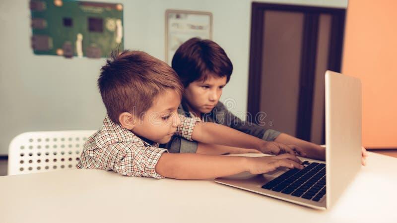 Due ragazzi che si siedono alla Tabella e che per mezzo del computer portatile a casa immagine stock