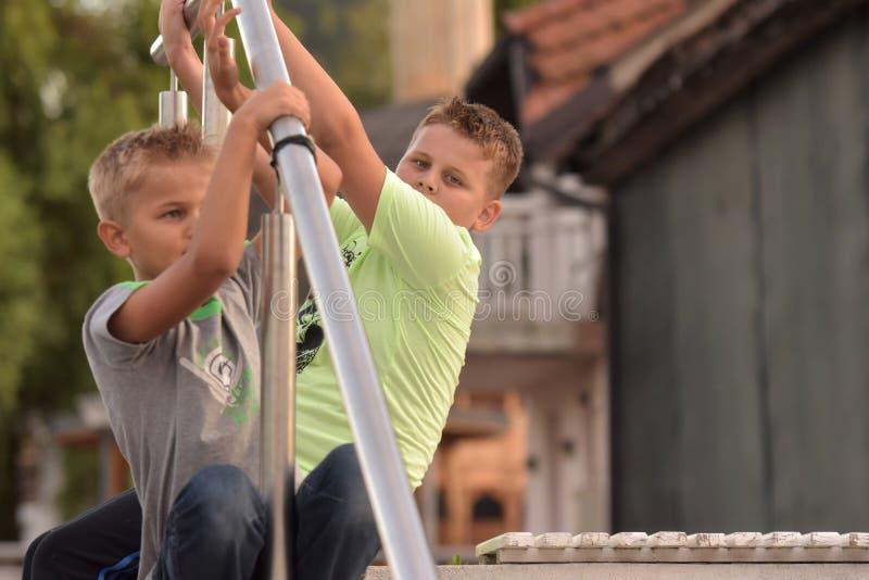 Due ragazzi che si siedono e che tengono la ferrovia di recinto di alluminio immagini stock libere da diritti