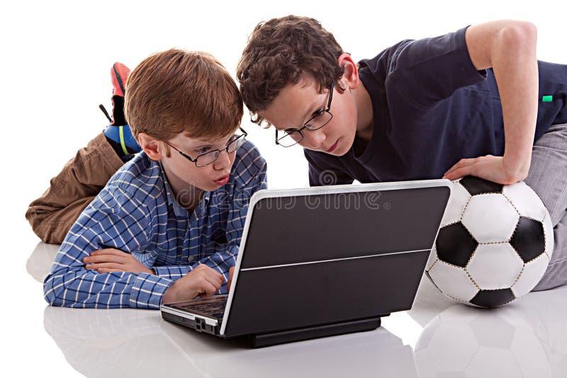 Due ragazzi che si siedono sul pavimento che gioca calcolatore, sopra fotografia stock
