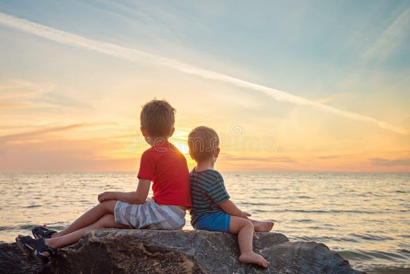 Due ragazzi che si siedono sulla roccia alla spiaggia al tramonto immagine stock libera da diritti