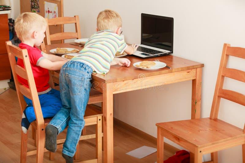 Due ragazzi che usando giocare del computer portatile fotografia stock