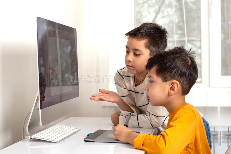 Due ragazzi dei ragazzi che fanno il loro compito con un computer Essi che attingono un computer facendo uso di una compressa fotografie stock