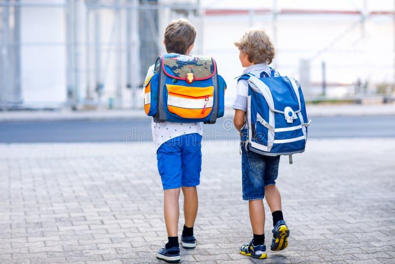 Due ragazzi del bambino con lo zaino o la cartella Scolari sul modo alla scuola Bambini adorabili in buona salute, fratelli e fotografie stock libere da diritti