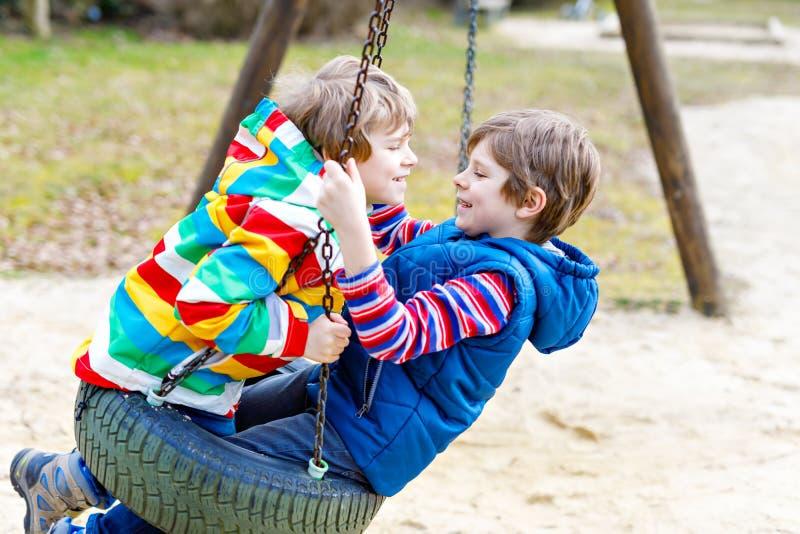 Due ragazzi del bambino divertendosi con l'oscillazione a catena sul campo da giuoco all'aperto immagini stock