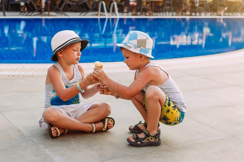 Due ragazzi della scuola materna in cappelli e gelato in un cono della cialda Bambini ed estate fotografia stock