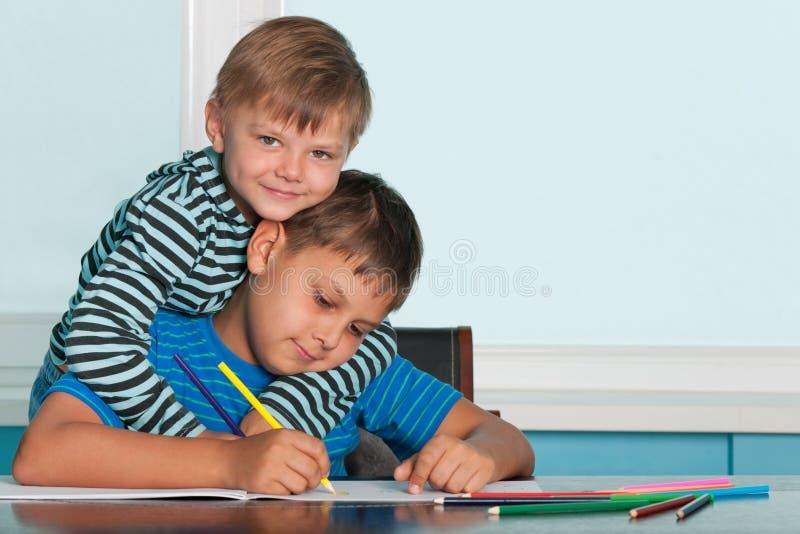 Due ragazzi dissipanti allo scrittorio immagini stock