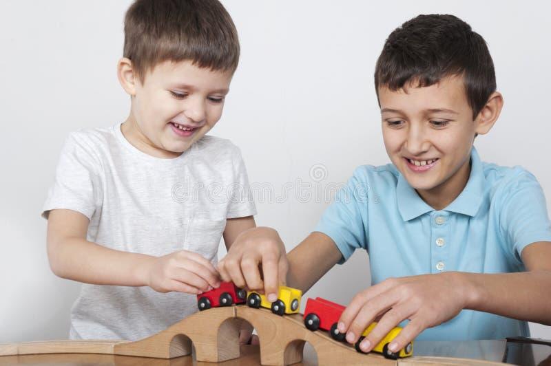 Due ragazzi divertendosi gioco con un treno di legno fotografie stock