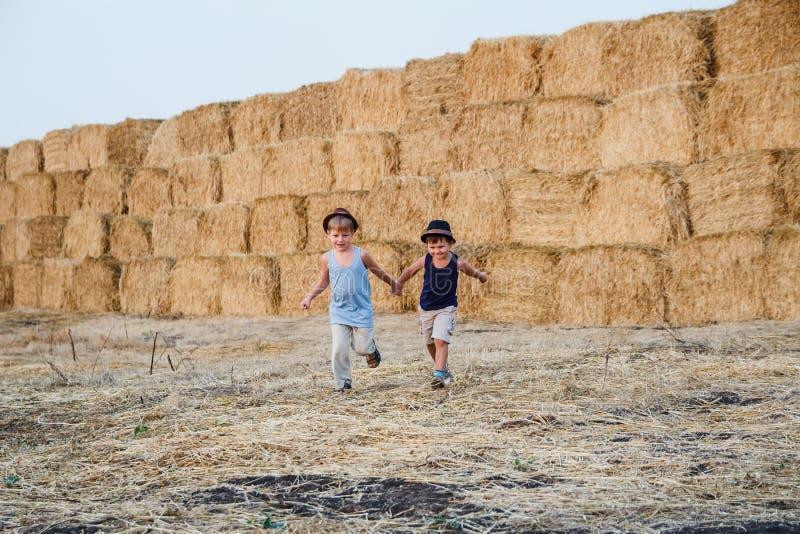 Due ragazzi divertenti che corrono, tenendosi per mano immagini stock libere da diritti