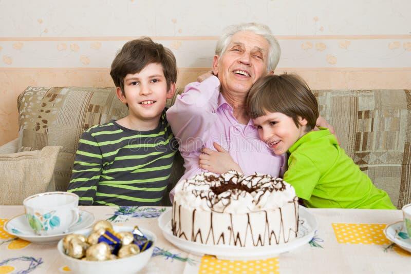 Due ragazzi e l'uomo senior con una festa agglutinano fotografie stock libere da diritti