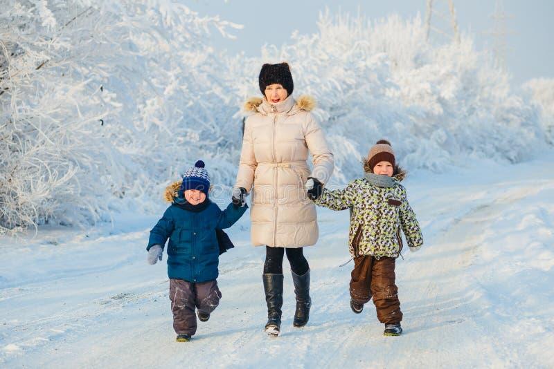Due ragazzi e nonna nella foresta di inverno immagini stock