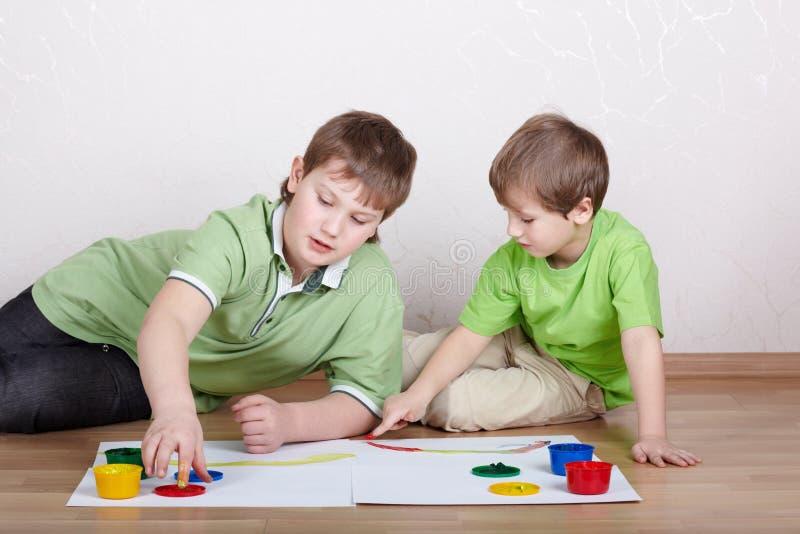Due ragazzi estraggono le vernici sui fogli di carta fotografia stock