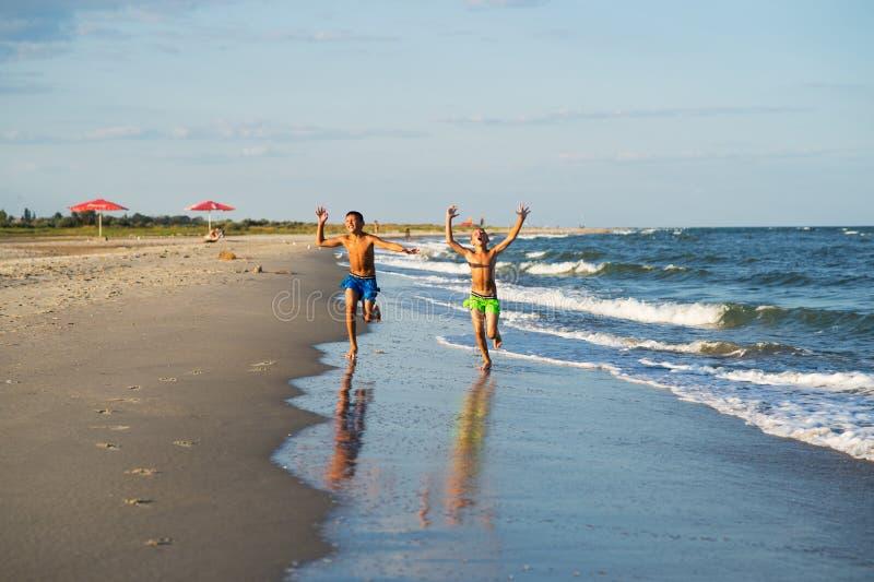Due ragazzi felici che corrono sulla spiaggia del mare fotografia stock