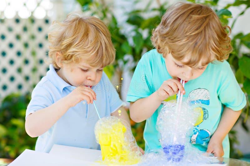 Due ragazzi felici dei bambini che fanno esperimento con le bolle variopinte immagine stock