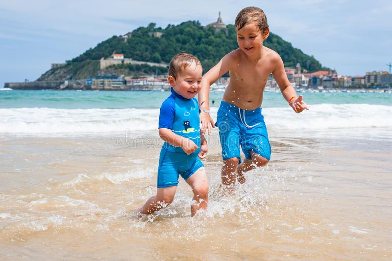 Due ragazzi felici nel funzionamento lungo una spiaggia che rende grande spruzza fotografia stock